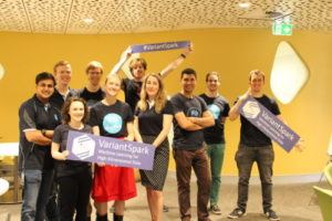 Ten happy looking team members who were behind Variant Spark stand in a yellow room holding signs that say VariantSpark